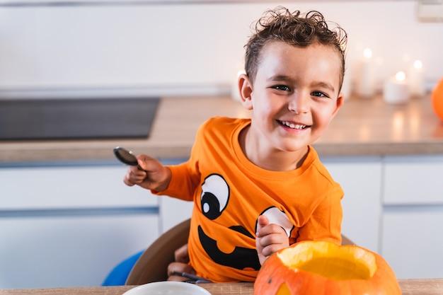 Porträt eines jungen, der glücklich in die kamera schaut, gekleidet wie ein halloween-kürbis-t-shirt, das sich entleert und dekor...