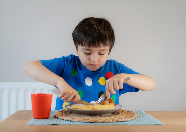 Porträt eines jungen, der hausgemachte fish and chips für das sonntagsessen zu hause hat.