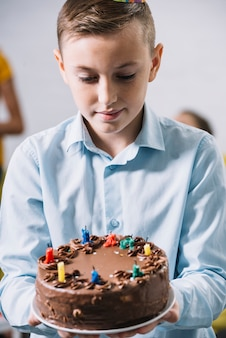 Porträt eines jungen, der köstlichen kuchen auf platte betrachtet