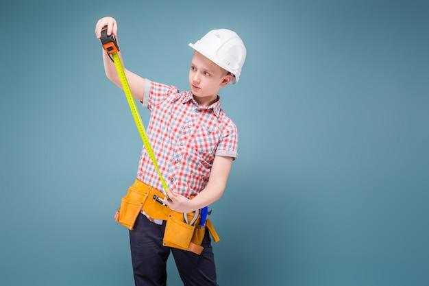 Porträt eines jungen erbauers in einem sturzhelm und in einem maßband in seiner hand
