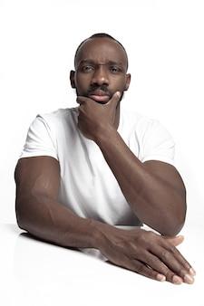 Porträt eines jungen ernsten afrikanischen mannes im studio. männliches modell der hohen mode, das auf weißem hintergrund aufwirft und lokalisiert