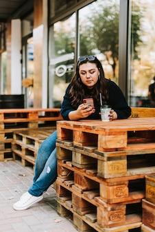 Porträt eines jungen erwachsenen mädchens mit einer tasse kaffee nahe einem café bei gutem herbstwetter