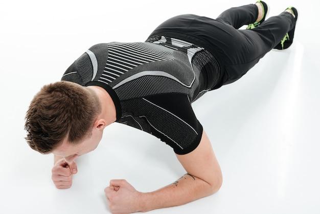 Porträt eines jungen fitnessmannes, der plankenübung tut