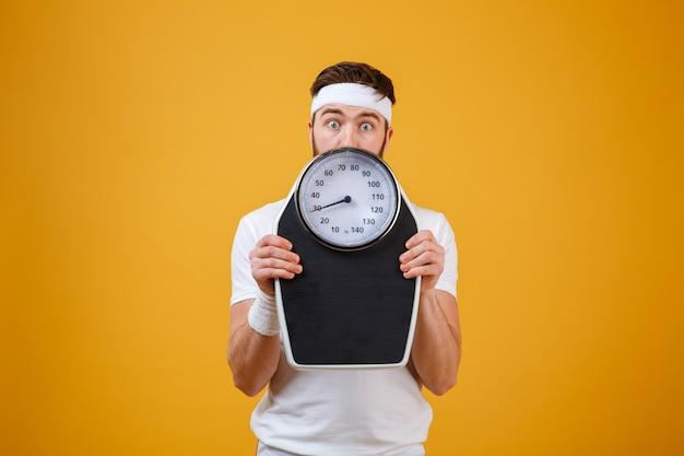 Porträt eines jungen fitnessmannes, der sich hinter gewichtswaagen versteckt