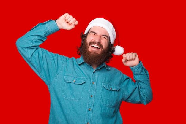 Porträt eines jungen fröhlichen bärtigen mannes, der weihnachtsmann-hut trägt und auf rotem hintergrund feiert