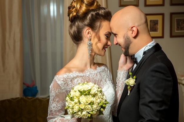 Porträt eines jungen, gerade verheirateten paares, das sich verliebt, umarmt und lächelt