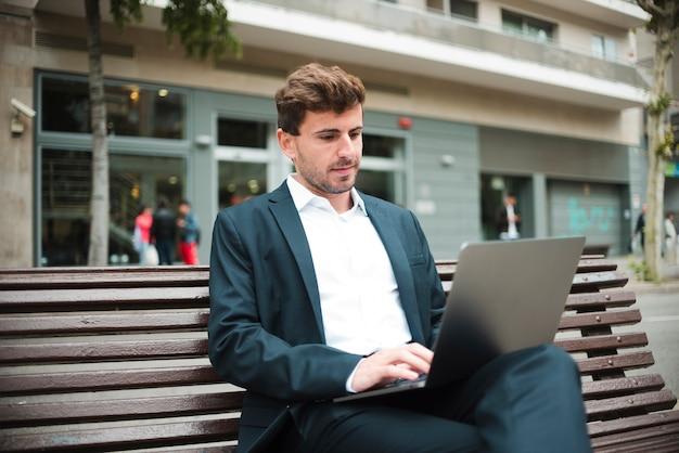Porträt eines jungen geschäftsmannes, der auf bank unter verwendung des laptops sitzt
