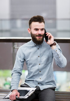 Porträt eines jungen geschäftsmannes, der auf der bank hält das klemmbrett und digitale tablette spricht am handy sitzt