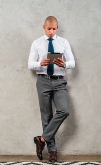 Porträt eines jungen geschäftsmannes, der auf der grauen wand betrachtet digitale tablette sich lehnt