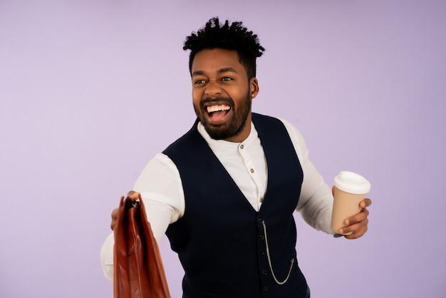 Porträt eines jungen geschäftsmannes, der beim halten einer tasse kaffee lächelt und gegen lokalisierten hintergrund lächelt. geschäftskonzept.