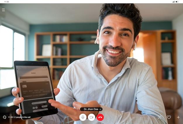 Porträt eines jungen geschäftsmannes, der etwas auf einem digitalen tablet-bildschirm bei einem arbeitsvideoanruf zeigt, während er zu hause bleibt. heimbüro. neuer normaler lebensstil.