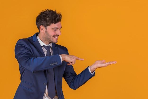 Porträt eines jungen geschäftsmannes, der seinen finger auf etwas gegen einen orange hintergrund zeigt