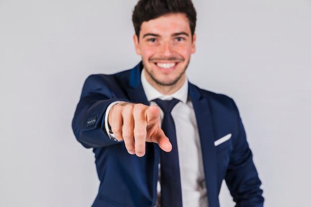 Porträt eines jungen geschäftsmannes, der seinen finger in richtung zur kamera gegen grauen hintergrund zeigt