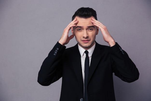 Porträt eines jungen geschäftsmannes, der über graue wand nachdenkt