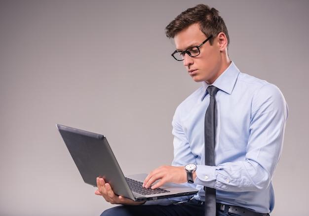 Porträt eines jungen geschäftsmannes mit einem laptop.