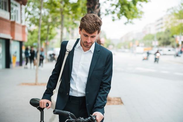 Porträt eines jungen geschäftsmannes mit seinem fahrrad, das auf straße steht