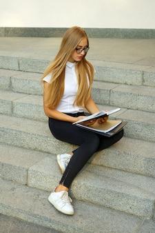 Porträt eines jungen gir-studentenmädchens, das auf treppe sitzt