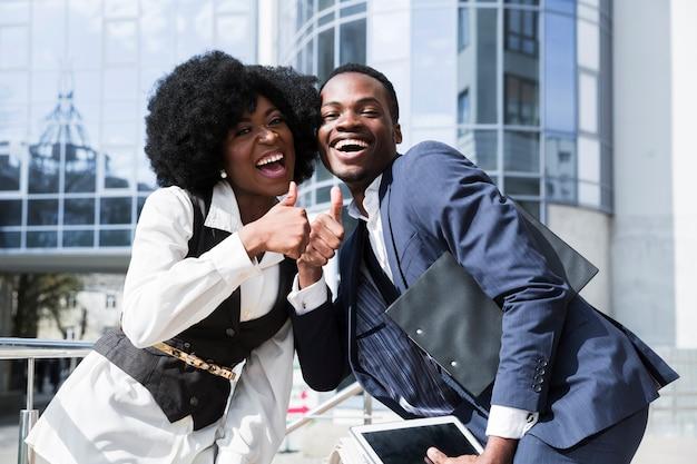Porträt eines jungen glücklichen afrikanischen mannes und der frau, die sich daumen zeigt