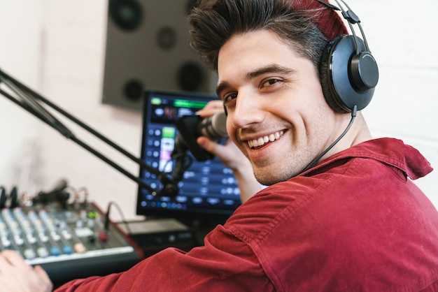 Porträt eines jungen glücklichen kaukasischen dj-mannes mit kopfhörern, der beim radiosender arbeitet, während er podcast-aufnahmen für online-shows macht