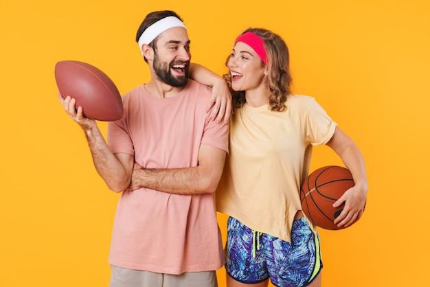 Porträt eines jungen glücklichen kaukasischen fitnesspaares, das stirnbänder trägt, die sportbälle isoliert halten