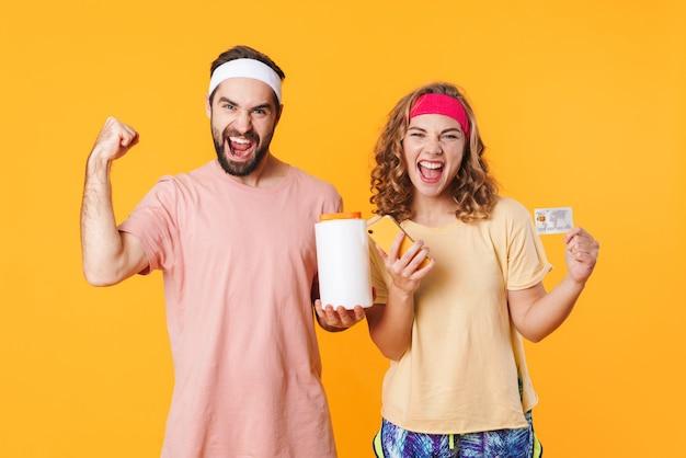 Porträt eines jungen glücklichen kaukasischen fitnesspaares mit stirnbändern, das proteinglas und kreditkarte isoliert hält