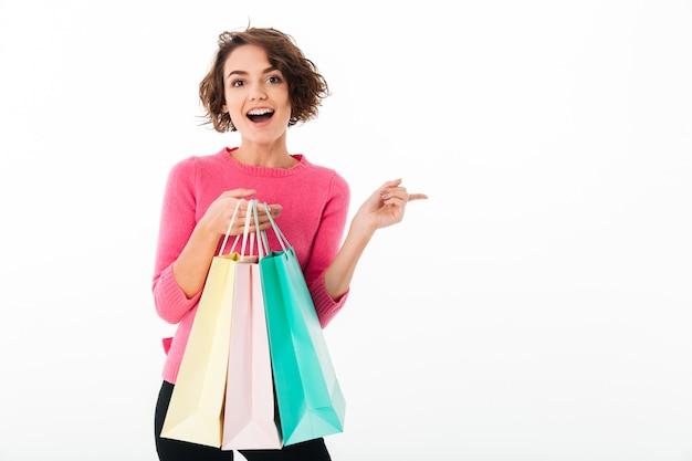 Porträt eines jungen glücklichen mädchens, das einkaufstaschen hält
