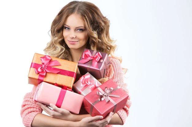 Porträt eines jungen glücklichen mädchens mit geschenkbox in den händen. studioporträt vor weißem hintergrund