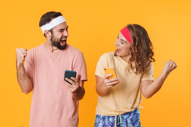 Porträt eines jungen, glücklichen, sportlichen paares, das stirnbänder trägt und sich freut, während es isolierte mobiltelefone verwendet