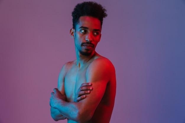 Porträt eines jungen gutaussehenden afroamerikanischen mannes mit nacktem oberkörper, der mit seinen verschränkten armen isoliert über der violetten wand posiert