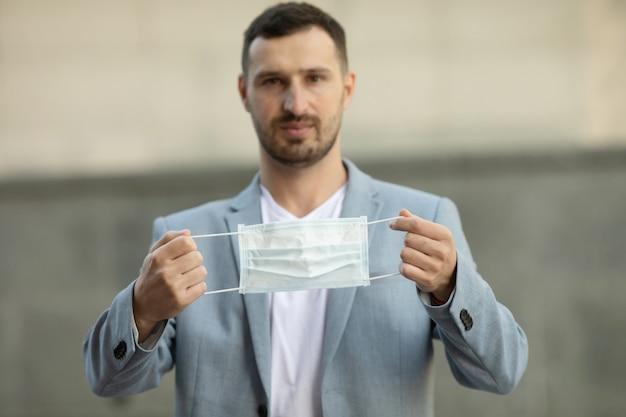 Porträt eines jungen gutaussehenden brünetten mannes, der medizinische gesichtsmaske in der hand hält