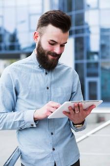 Porträt eines jungen gutaussehenden mannes, der digitale tablette verwendet