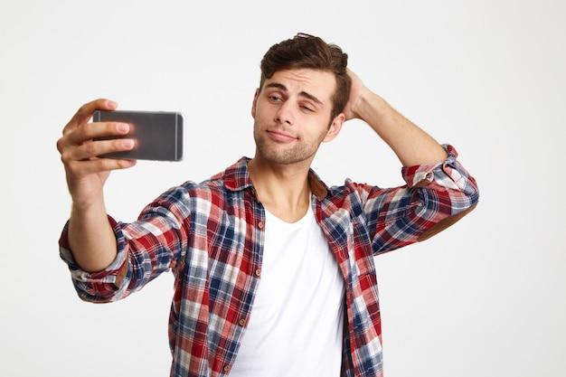 Porträt eines jungen gutaussehenden mannes, der ein selfie nimmt