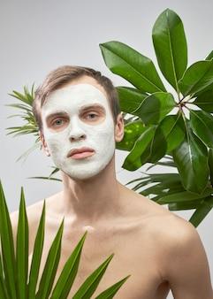 Porträt eines jungen gutaussehenden mannes mit weißer kosmetischer maske auf seinem gesicht vor dem hintergrund grüner pflanzen. gesichtspflege für männer