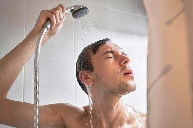 Porträt eines jungen gutaussehenden mannes wäscht sich mit duschgel, schäumt den kopf mit shampoo im badezimmer zu hause in nahaufnahme ein