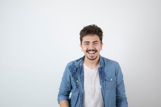 Porträt eines jungen gutaussehenden mannmodells mit dem schnurrbart, der kamera steht und betrachtet.