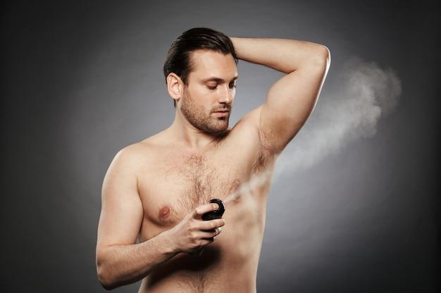 Porträt eines jungen hemdlosen mannes, der deodorant sprüht