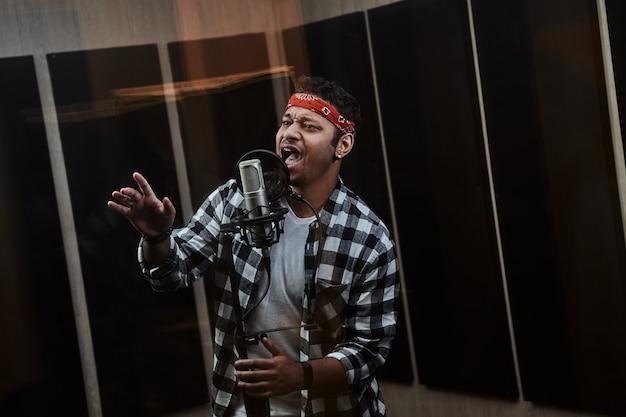 Porträt eines jungen hip-hop-künstlers, der konzentriert in ein kondensatormikrofon singt, während