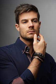 Porträt eines jungen hispanischen mannes in einem formellen outfit mit ernstem gesichtsausdruck