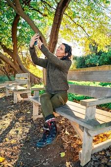 Porträt eines jungen hübschen kaukasischen mädchens, das auf einer parkbank sitzt und ein selfie bei sonnenuntergang nimmt