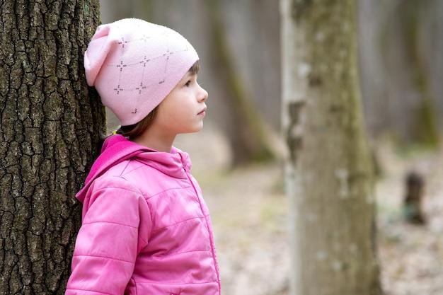 Porträt eines jungen hübschen mädchens mit rosa jacke und mütze, das sich an einen baum im wald lehnt