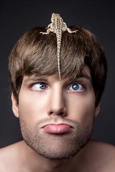 Porträt eines jungen hübschen mannes mit eidechse auf seinem gesicht