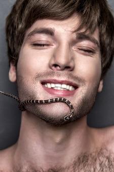 Porträt eines jungen hübschen mannes mit schlange auf seinem gesicht
