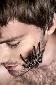Porträt eines jungen hübschen mannes mit spinne auf seinem gesicht