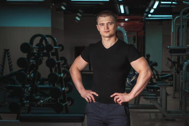 Porträt eines jungen hübschen muskulösen eignungstrainerabschlusses oben.