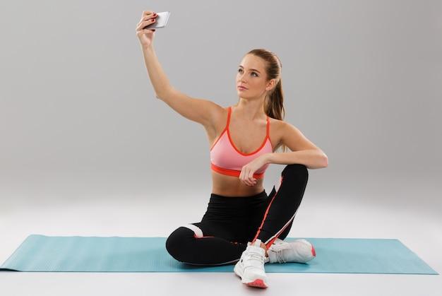 Porträt eines jungen hübschen sportmädchens, das selfie nimmt