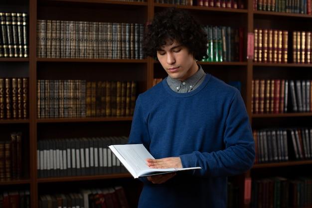 Porträt eines jungen in einem blauen pullover, der mit einem buch in seinen händen steht