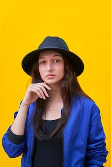 Porträt eines jungen kaukasischen mädchens im schwarzen hut und in der blauen jacke, hand über gesicht