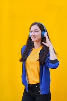 Porträt eines jungen kaukasischen mädchens mit langen brünetten haaren, blauer jacke und schwarzer jeans, musik mit ihren blauen kopfhörern hörend.