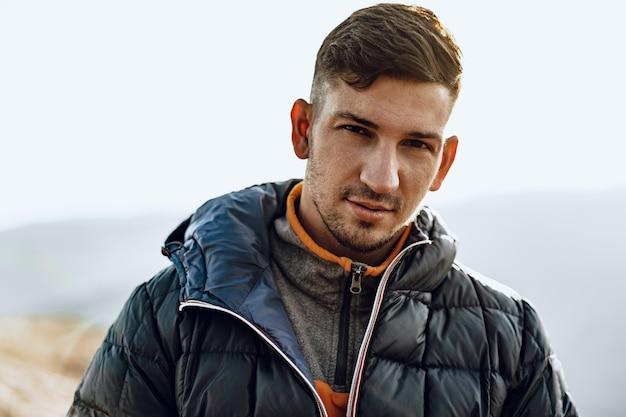 Porträt eines jungen kaukasischen mannes, der in den bergen wandert