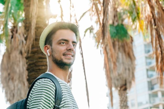 Porträt eines jungen kaukasischen mannes mit palmen im hintergrund